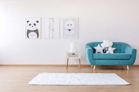 Poster an der weißen Wand im Kinderzimmer mit Teppich und Sternenkissen auf blauem Sofa. Echtes Foto
