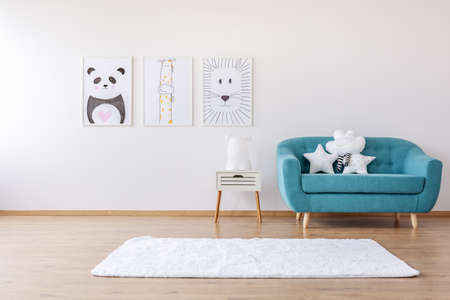 Posters on white wall in kid's room interior with rug and stars pillows on blue sofa. Real photo