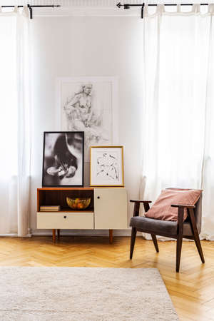 Armchair with cushion next to cabinet with posters in bright flat interior with windows. Real photo