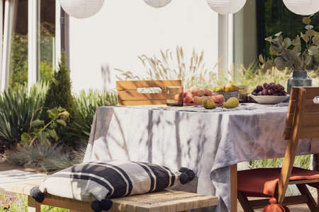 Patterned pillow on wooden bench at table with fruits on the terrace of house with plants. Real photo
