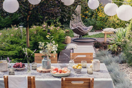 Lanterns above table with flowers, food and drink in the garden with hanging chair and plants. Real photo