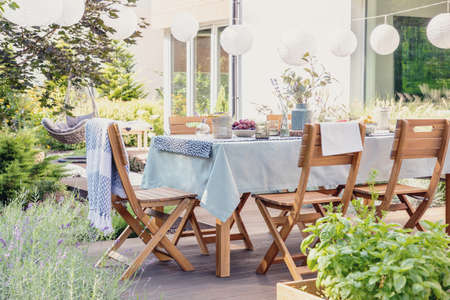 Wooden chairs at table with flowers and food in the garden with plants and lanterns. Real photo
