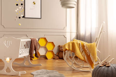 Honeycombs, rocking chair and a crib in a child room interior. Real photo Banco de Imagens