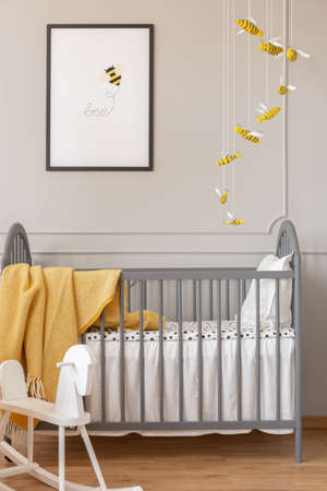 Grey crib, bee decoration and graphic, and rocking horse in a kid room interior Archivio Fotografico - 123561311