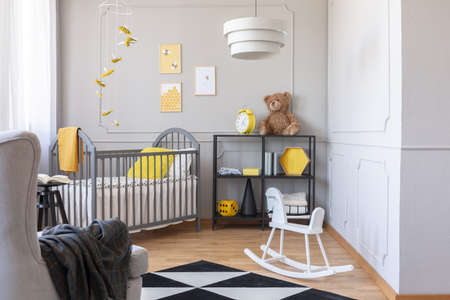 Real photo of a grey and yellow kid's room interior Stock Photo - 123561315