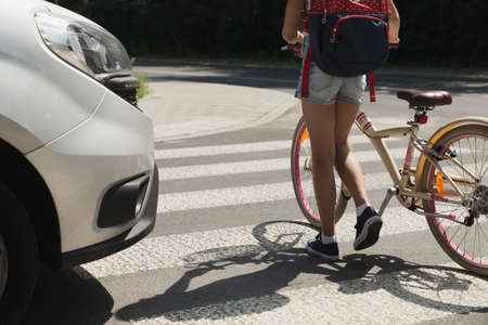 Teenager schoolgirl with backpack and bike crossing street in front of a car