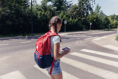 Teenage schoolgirl with backpack using phone during her way to school