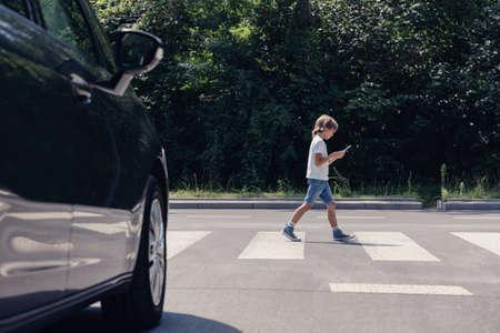 Ángulo bajo de coche delante del paso de peatones y niño caminando con smartphone