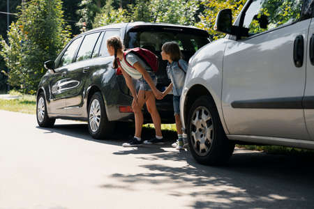 Children with backpacks between cars trying to walk through the road Фото со стока