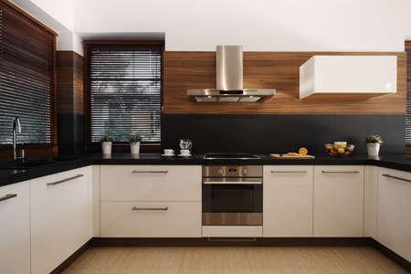 Cocina elegante en blanco y negro con detalles en madera y horno y fregadero plateados