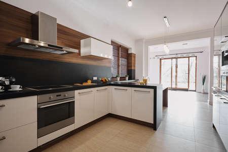 Elegancka biało-czarna kuchnia z drewnianymi akcentami i otwartą przestrzenią pustego salonu z oknami od podłogi do sufitu