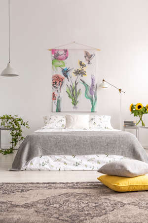 Grey and yellow pillows placed on carpet in real photo of white bedroom interior with material painting, king-size bed with floral bedding, fresh sunflowers and lamps