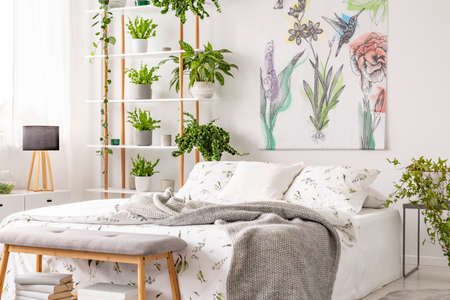 Grey blanket thrown on double bed with floral bedclothes standing in white room interior with painting, many fresh plants on wooden rack in the real photo