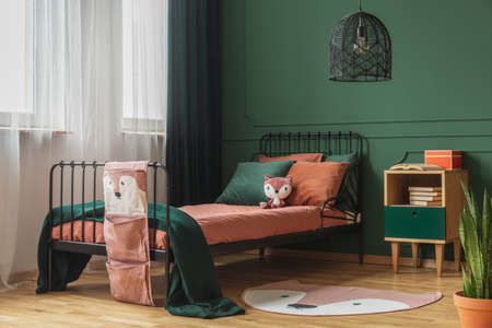 Real photo of a rug shaped like a fox on the wooden floor of a child's bedroom interior with orange sheets and pillows on a black bed standing next to the window