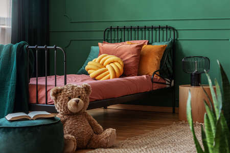 Big, brown teddy bear and an open book on a green, velvet pouf in front of a metal frame bed in child's bedroom interior. Real photo