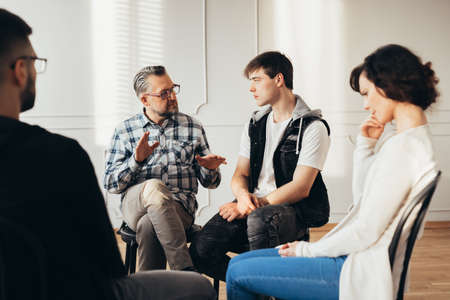 Psychologist talking about twelve-step program to addicted man during group support meeting Stock Photo