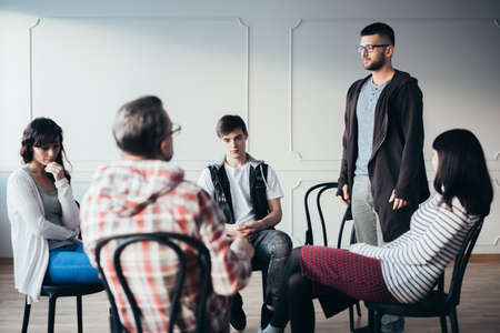 Young man admitting that he is an alcoholic during support group meeting