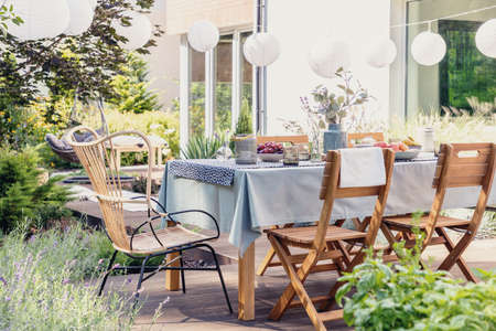 Table with wooden chairs in bright green garden of modern house, real photo