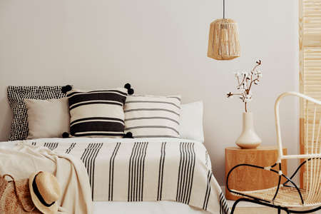 Patterned pillows and blanket on king size bed, cotton flower in vase on wooden nightstand, copy space on empty wall