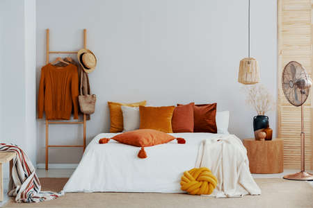 Autumn colors in bright natural bedroom with wooden accents, copy space on empty wall