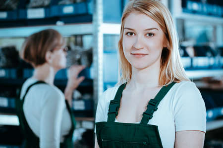 Young blonde female factory worker wearing green uniform at job