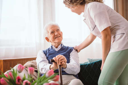 Senior man with a walking stick being comforted by nurse in the hospice Stockfoto
