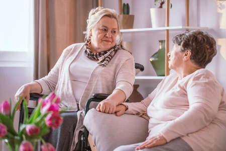 Elderly lady on the wheelchair holding hand her friend in nursing home 写真素材