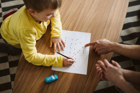 Cute boy kneeling on the floor and connecting dots on a piece of paper