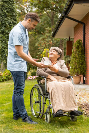 Assistant giving cup of tea to happy senior woman in the wheelchair in the garden