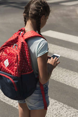Kid with backpack using smartphone while walking through pedestrian crossing