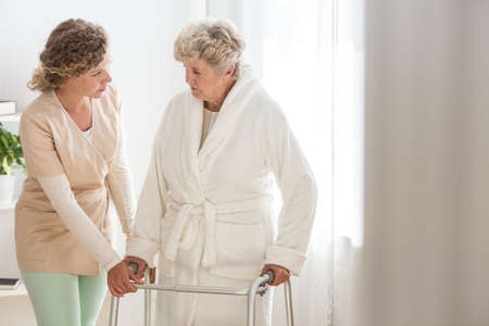 Senior woman in bathrobe with walker and helpful nurse supporting her
