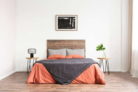 Minimal classic bedroom with wooden bed, coral linen sheets and black and white artwork
