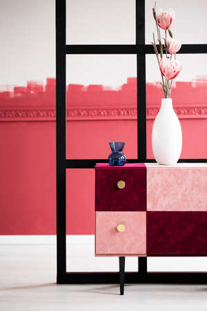 Pink flowers in white vase next to blue vase on handmade pink and burgundy commode Stok Fotoğraf - 124624107