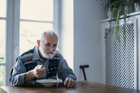 Senior grandfather with grey hair and beard sitting alone in the kitchen eating breakfast Stock Photo