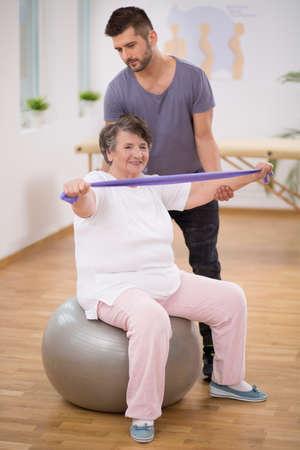 Professional physiotherapist stabilizing senior woman sitting on exercising ball Stock Photo
