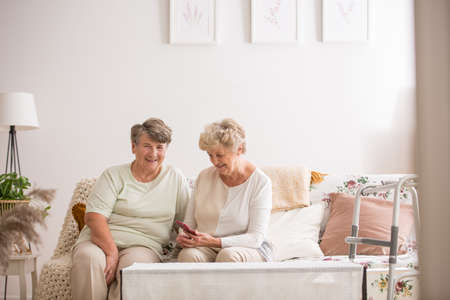 Two senior friends sitting together at couch Stock Photo