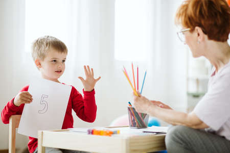 Boy in red sweater learning to count during extra-curricular activities