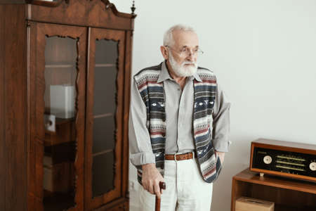 Sad senior man with walking stick standing alone at home Stock Photo