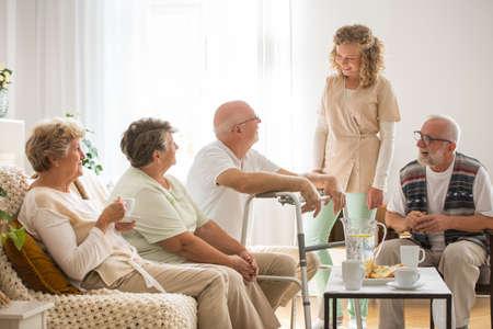Ältere Patienten mit hilfsbereiter junger Krankenschwester im Pflegeheim Standard-Bild