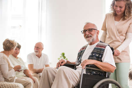 Senior man on wheelchair with helpful caregiver supporting him
