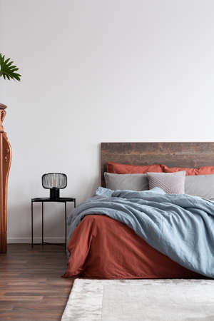Vertical capture of a contemporary white bedroom with coral and light blue bedclothes