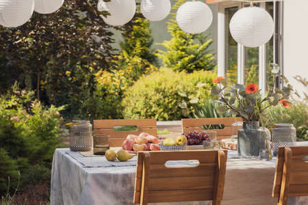 Garden with stylish wooden furniture and table with fruits and flowers, real photo Stock Photo
