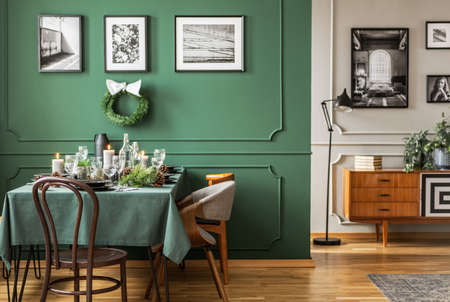 Open plan living and dining room interior with table with chairs and emerald green armchair