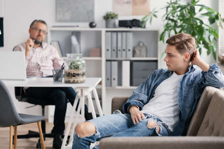 Professional therapist and teenage boy ignoring him during appointed meeting