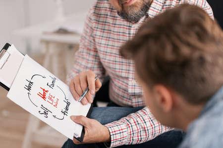 Trener życia osobistego wyjaśniający wykres swojemu młodemu pacjentowi