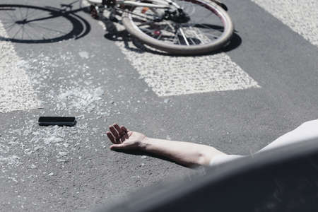 Hand of victim on pedestrian crossing next to bike after dangerous traffic accident Фото со стока