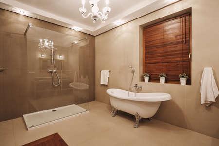 Modne beżowo-drewniano-białe wnętrze łazienki z wygodną wanną i przestronną kabiną prysznicową