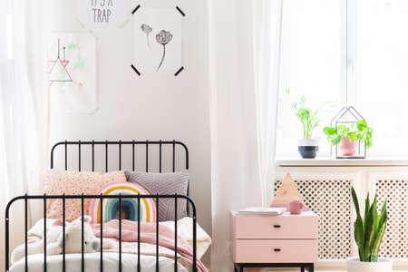 Lichte kinderkamer met kleurrijk beddengoed, prints aan de muur en pastelroze nachtkastje, echte foto Stockfoto
