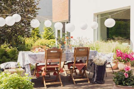 Weiße Lampen über dem Tisch und Holzstühle auf der Terrasse mit Blumen neben dem Haus