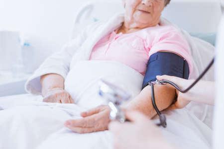 Ältere Frau mit Blutdruckmessgerät am Arm und junge Praktikantin im Krankenhaus